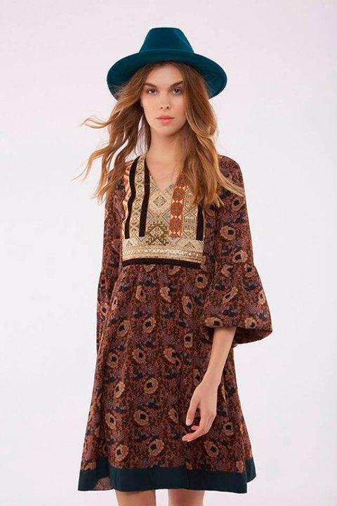 Vestido floral sobre fondo cobre, con pasamanería en pecho y espalda.