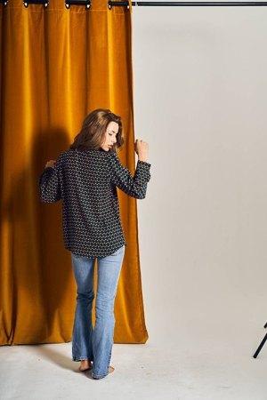 Camisa Iñaki, vista por la espalda. Estampado de cerezas mostaza sobre fondo azul.