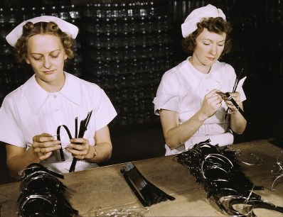 Two Navy wives, Eva Herzberg and Elve Burnham, entered war work after their husbands joined the service, Glenview, Ill. in October 1942. They assemble bands for blood transfusion bottles at Baxter Laboratories. Mrs. Burnham is the mother of two children. (Howard R. Hollem/U.S. Office of War Information/Library of Congress)