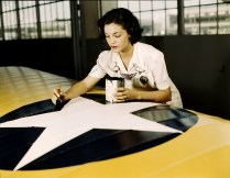 Painting the American insignia on airplane wings is a job that Mrs. Irma Lee McElroy, a former office worker, does with precision and patriotic zeal. Mrs. McElroy is a civil service employee at the Naval Air Base, Corpus Christi, Texas in August 1942. Her husband is a flight instructor. (Howard R. Hollem/U.S. Office of War Information/Library of Congress)