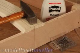 Nägel und Holzleim fixieren die Trasse bündig auf dem Rahmen.