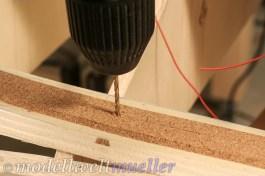 Mittig ein kleines Loch für die Kabel bohren.
