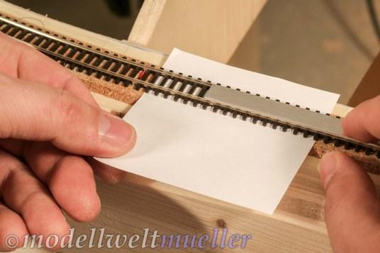 Mit Schablonen wird das Gleis gerichtet und dann das Papier herausgezogen.