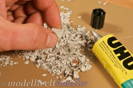 Den Würfel mit Kleber in die Papierschnitzel drücken