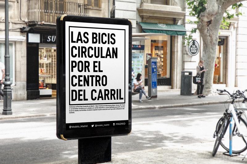 """Mockup de MUPI publicitario mostrando el mensaje """"las bicis circulan por el centro del carril"""". Plantilla de https://mockupgratis.com. Campaña pedida al Ayuntamiento de Madrid para favorecer la seguridad del ciclismo urbano en Madrid."""