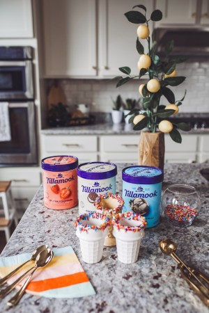 How to Throw a Fun and Easy Summer Soiree by popular Nashville blog Modern Day Moguls: image of three cartons of Tillamook ice cream, gold spoons, colorful stripe napkins, ice cream scoop, bowl of sprinkles, and sprinkle topped ice cream cones on a marble kitchen countertop.