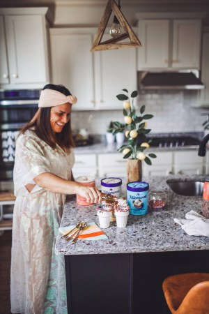 How to Throw a Fun and Easy Summer Soiree by popular Nashville blog Modern Day Moguls: image of three cartons of Tillamook ice cream, gold spoons, colorful stripe napkins, ice cream scoop, bowl of sprinkles, and woman putting ice cream scoops into sprinkle topped ice cream cones on a marble kitchen countertop.