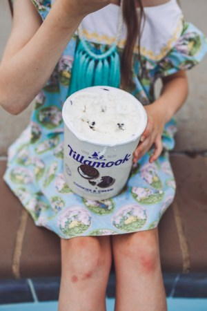 How to Throw a Fun and Easy Summer Soiree by popular Nashville blog Modern Day Moguls: image of young girl in a blue floral dress striped dress eating out of a carton of Tillamook vanilla ice cream with a spoon.