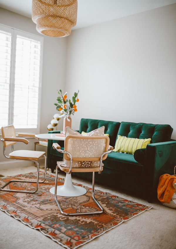 How to create a stylish and functional home office space by top US lifestyle blog, Modern Day Mogul: image of room with orange rug, wicker pendant light, green velvet couch, yellow throw pillows, orange throw, modern white table and modern white chairs from Joybird.