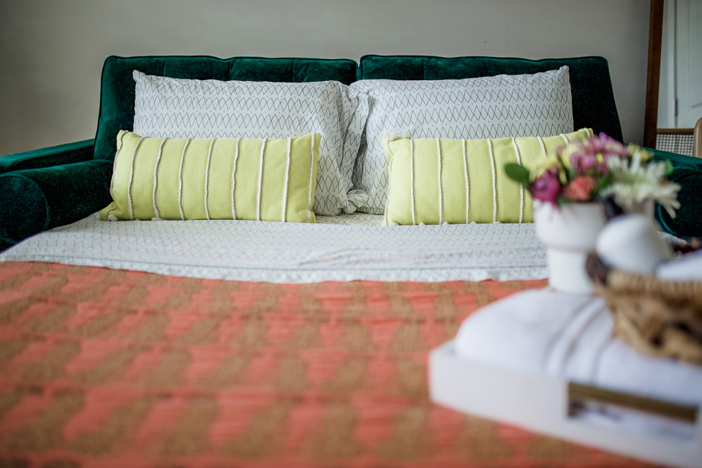 What to Look for When Buying Furniture Online by popular lifestyle blog, Modern Day Moguls: image of a joybird hide-a-bed with a orange quilt and lime green throw pillows.