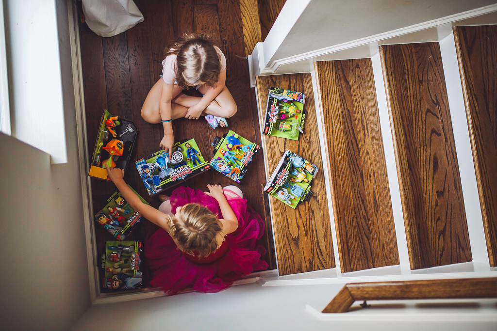 Rescue Heroes Toys: Play Time That Could Teach All Of Us Something by popular life and style blog, Modern Day Moguls:  image of two girls sitting by the bottom of a stair case and playing with Rescue Heroes toys.