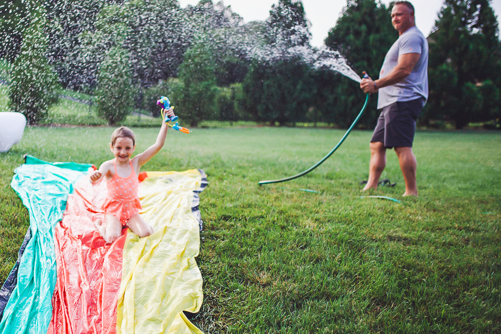 Rescue Heroes Toys: Play Time That Could Teach All Of Us Something by popular life and style blog, Modern Day Moguls:  image of a little girl holding a Sandy O'Shin Rescue Heroes toy while she goes down a slip n' slide.