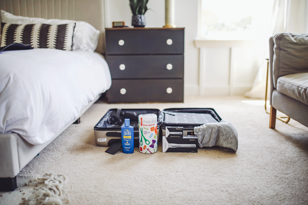 How to Be Prepared for Summer Adventures by popular lifestyle blog, Modern Day Moguls: image of an open suitcase with Hanes Ultimate Xtemp tees, UltraSwim Chlorine Removal Shampoo, Medipro First Aid Pods from Me4kidz, and MAGLITE® Solitaire LED & Mini Maglite® Pro LED in front of it.
