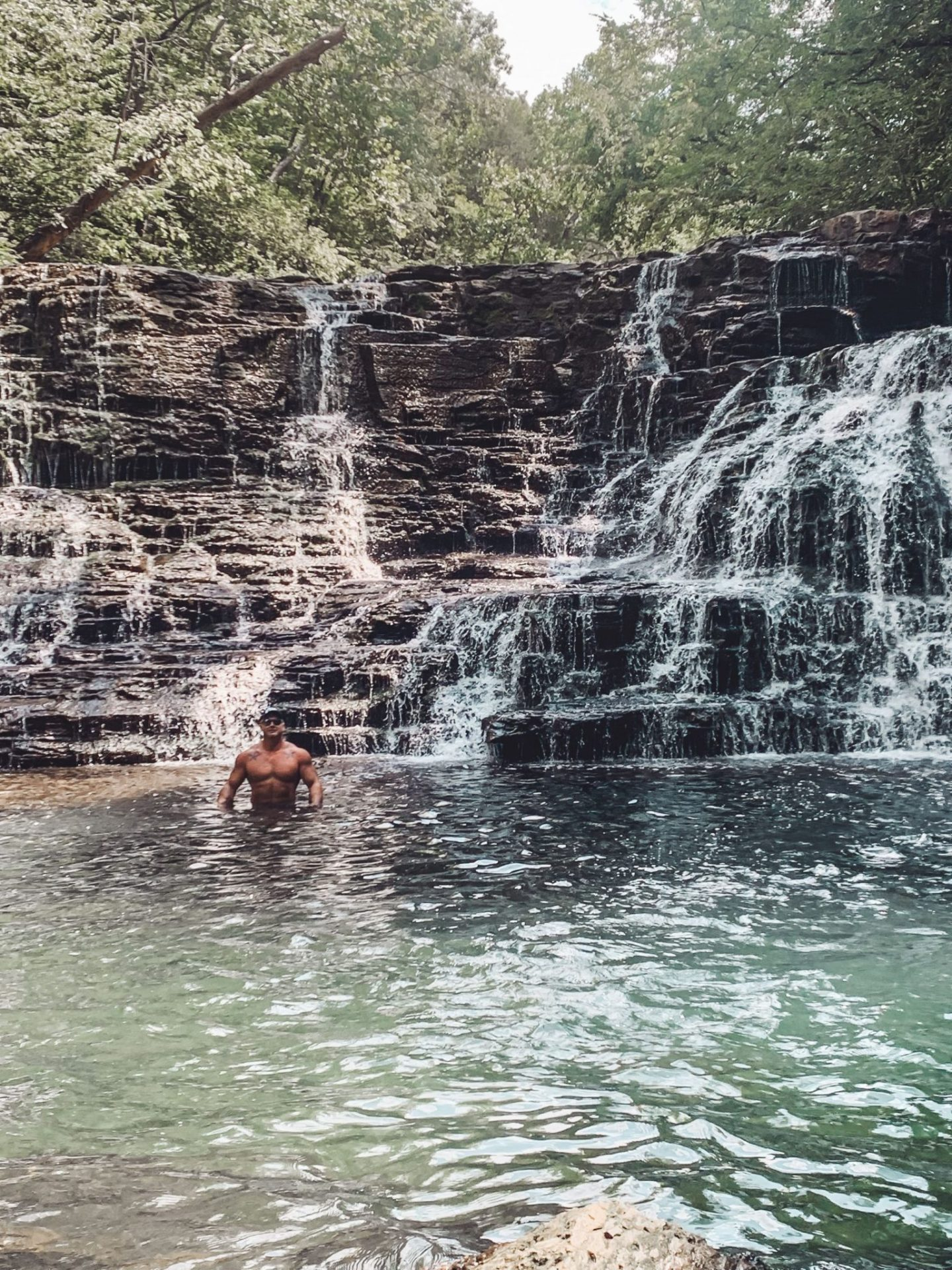 Family-Friendly Waterfall Hiking Trails in Nashville, TN by popular Nashville blog, Modern Day Moguls: image of a man standing in the water at the base of Rutledge Falls in Tullahoma, TN.
