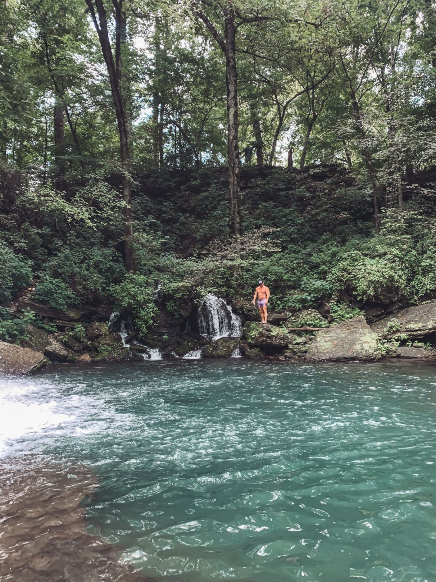 Family-Friendly Waterfall Hiking Trails in Nashville, TN by popular Nashville blog, Modern Day Moguls: image of a man standing on a rock next to Rutledge Falls in Tullahoma, TN.