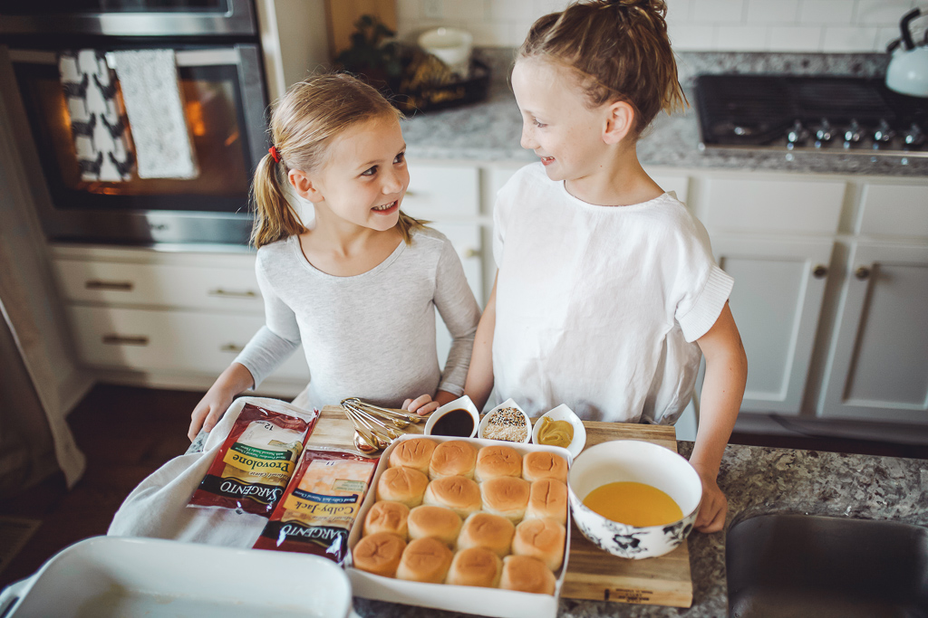 Kid Friendly Meal Prep Ideas : Back to School Edition by popular Nashville life and style blog, Modern Day Moguls: image of a mom and her two daughters in the kitchen making oven baked sandwiches with Sargento sliced cheese.