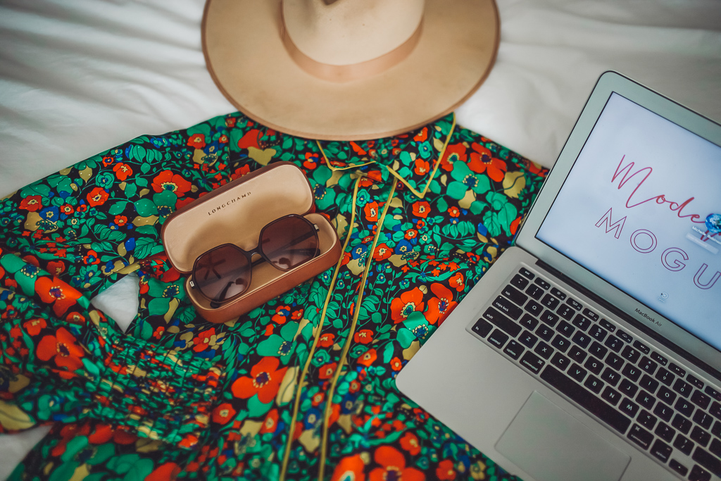 A Busy Moms Guide on How to Take Care of Your Family's Health by popular Nashville lifestyle blog, Modern Day Moguls: image of a fedora, sunglasses, laptop, and floral print dress on a bed.