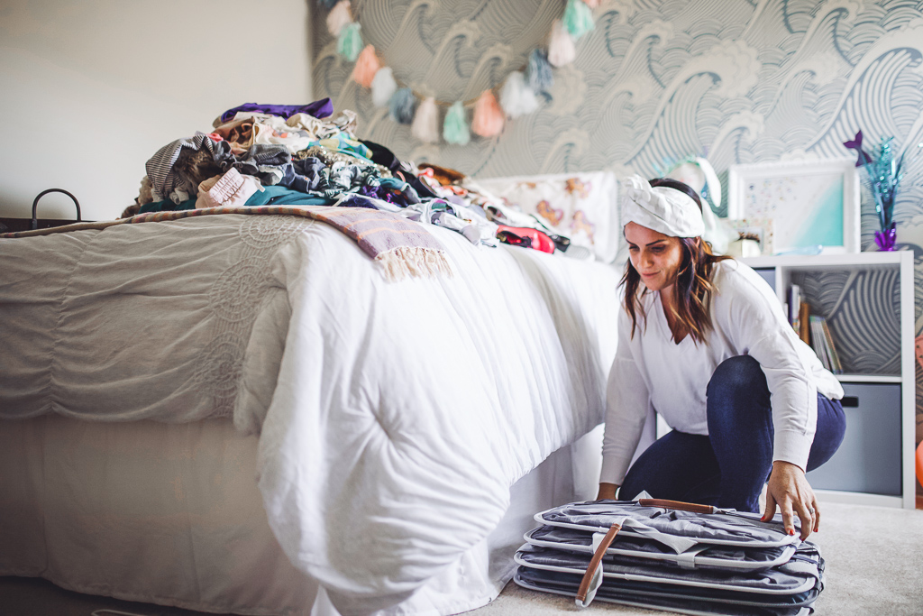 How to Organize Kids Closets Seasonally by popular lifestyle blog, Modern Day Moguls: image of a woman using some Clevermade Laundry Caddy - Collapsible Laundry Basket & Hampers.