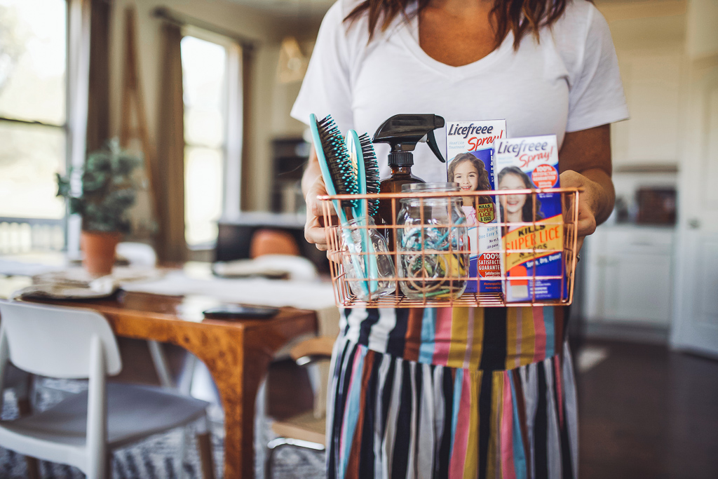 Home Remedy for Head Lice All Moms Need On Hand by popular Nashville life and style blog, Modern Day Moguls: image of a mom holding a basket filled with Licefree hair spray, brushes, a spray bottle, and a jar of hair elastics.