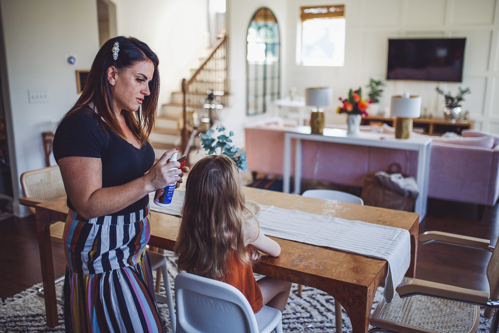 Home Remedy for Head Lice All Moms Need On Hand by popular Nashville life and style blog, Modern Day Moguls: image of a mom spraying Licefree in her daughter's hair.
