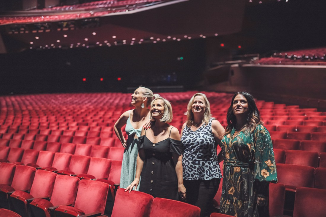 California Vacation Ideas for a Momcation in Orange County by popular Nashville travel blog, Modern Day Moguls: image of 4 women standing inside a theater.
