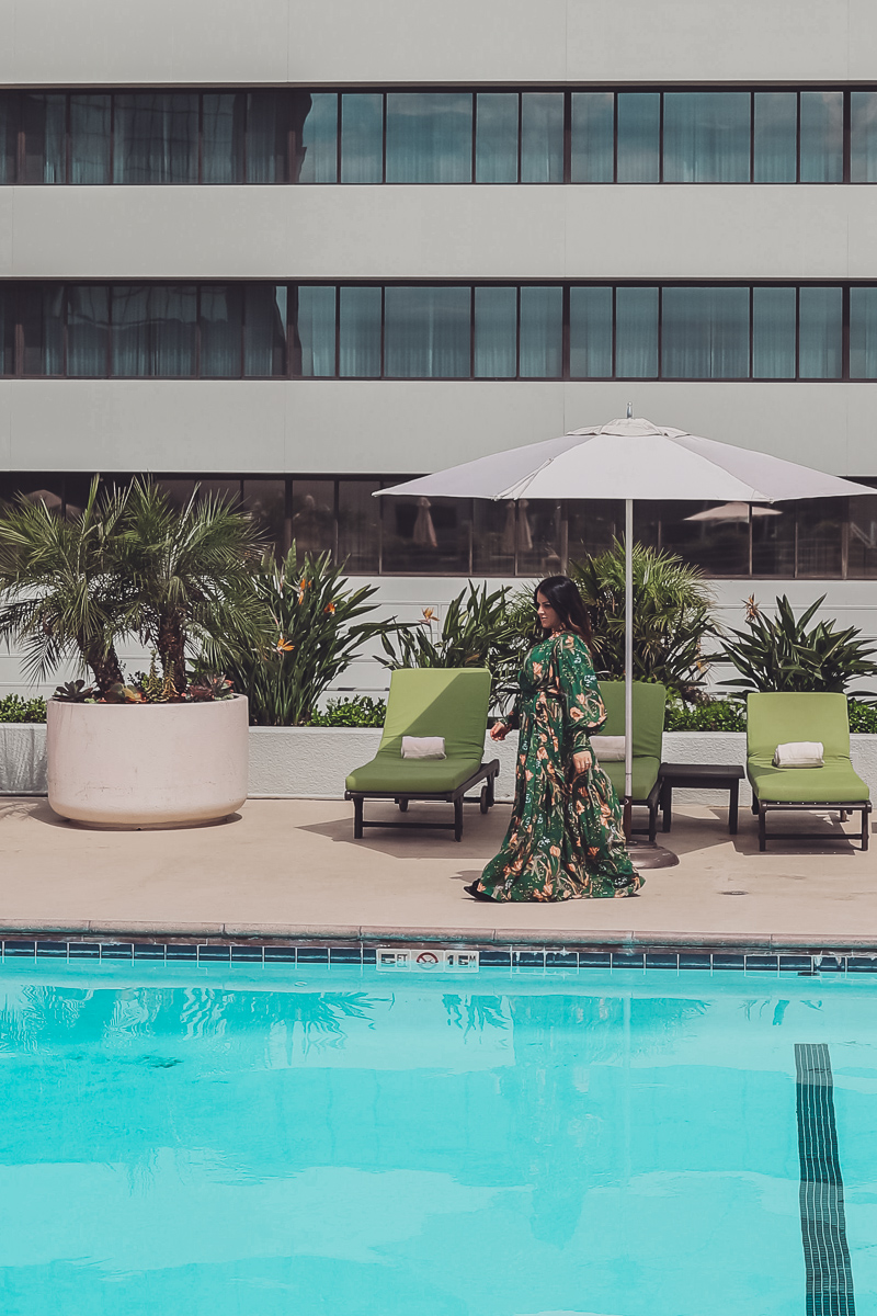 California Vacation Ideas for a Momcation in Orange County by popular Nashville travel blog, Modern Day Moguls: image of a woman walking by a swimming pool.