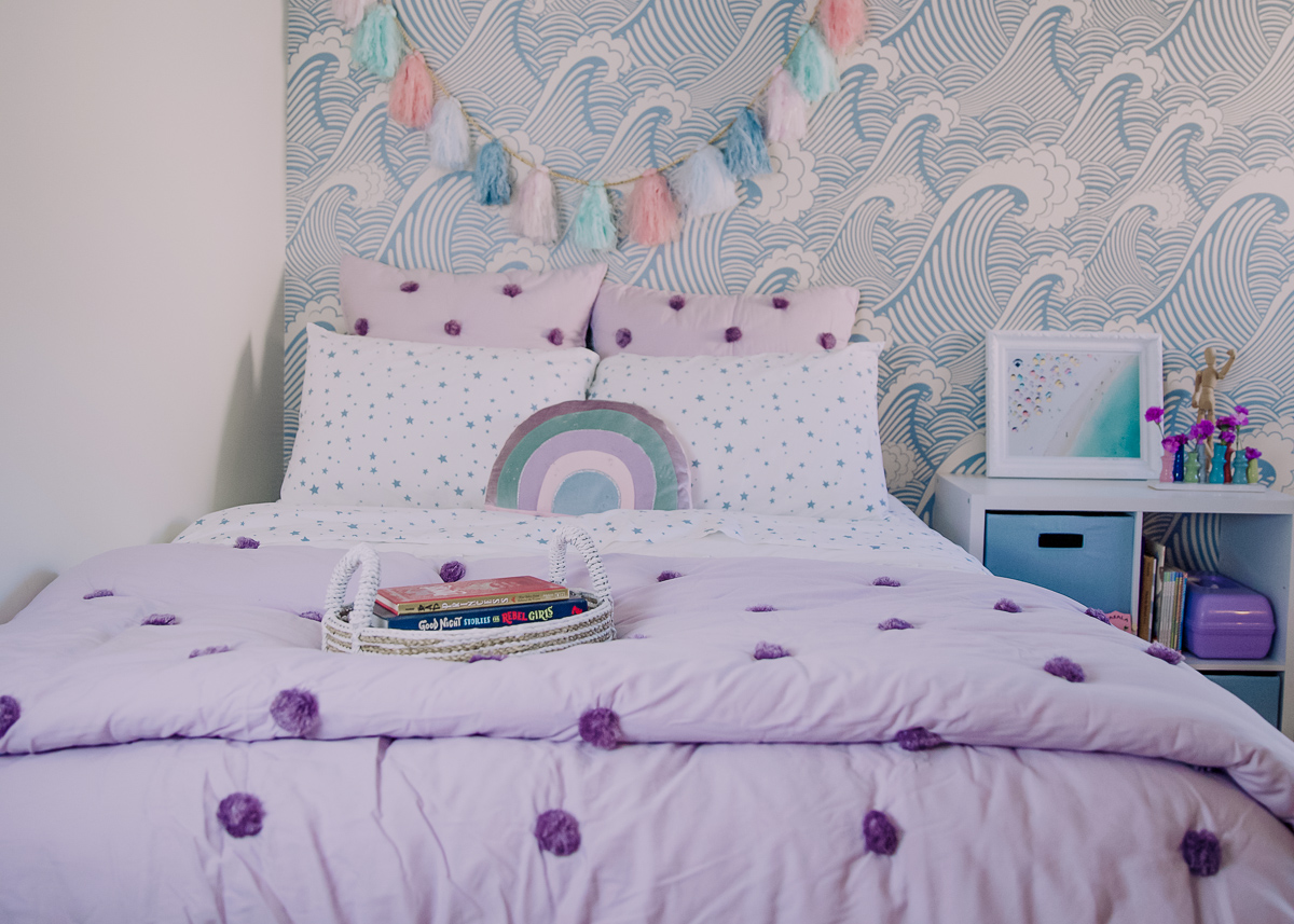 Girls Bedroom Redo: Mermaid, Unicorn, and Rainbows Oh My! by popular Nashville lifestyle blog, Modern Day Moguls: image of a bed with Pottery Barn Kids Shining Star Glow-in-the-Dark Sheet Set, and Pottery Barn Kids Washed Sateen Pom Pom Quilt.