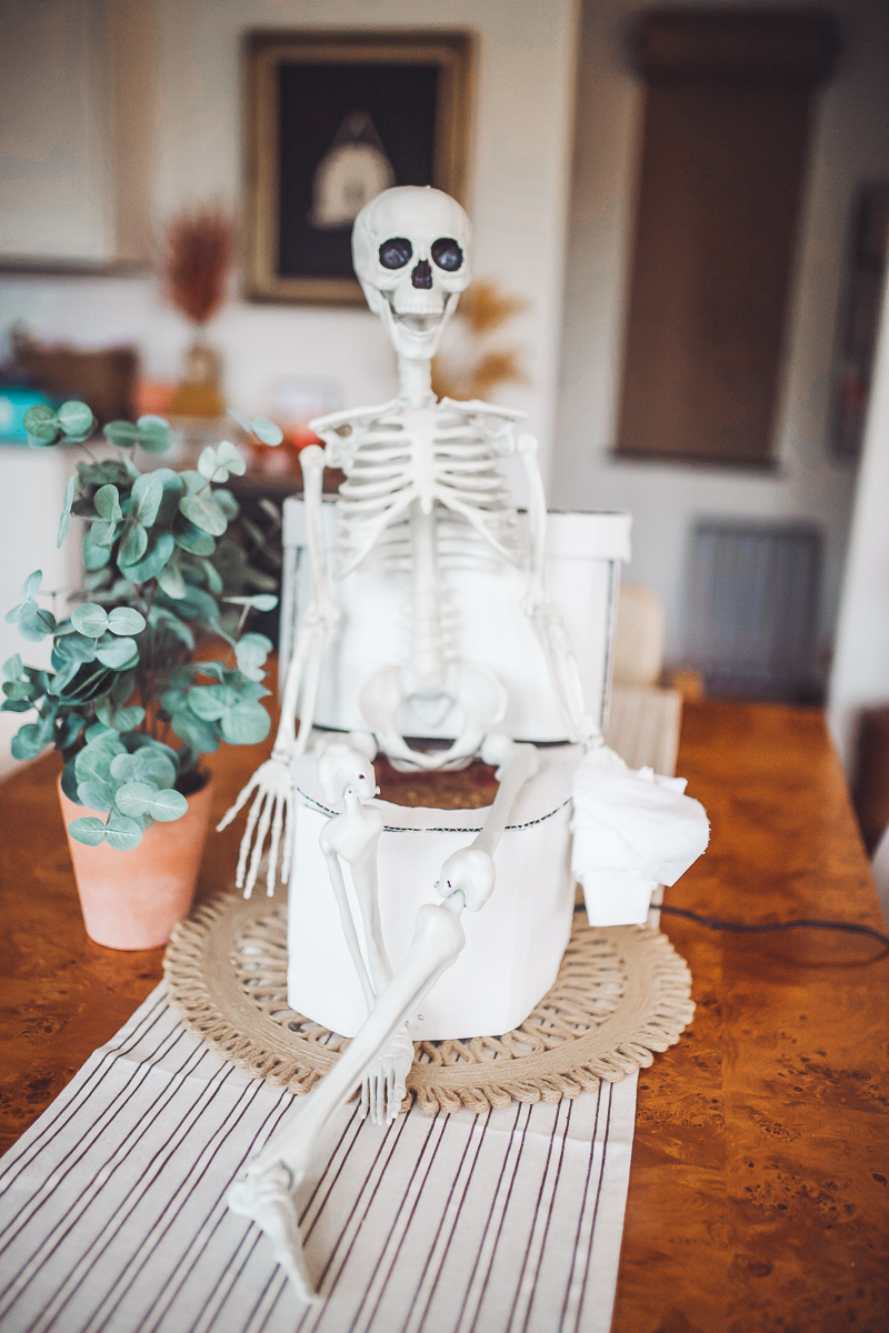 Spooky Skeleton Halloween Dip Recipe by popular Nashville lifestyle blog, Modern Day Moguls:image of a skeleton sitting on a cardboard toilet on top of a table.