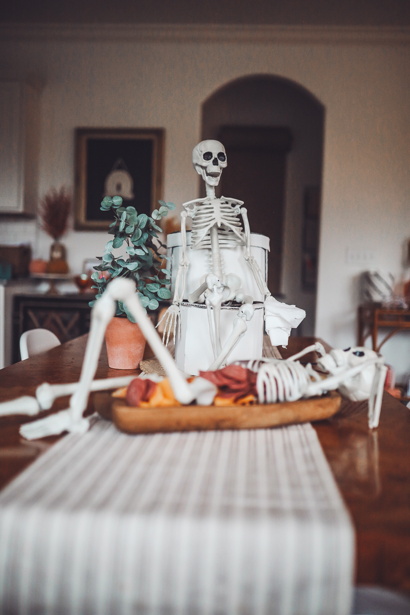 Spooky Skeleton Halloween Dip Recipe by popular Nashville lifestyle blog, Modern Day Moguls:image of a skeleton charcuterie board and a skeleton sitting on a cardboard toilet on top of a table.