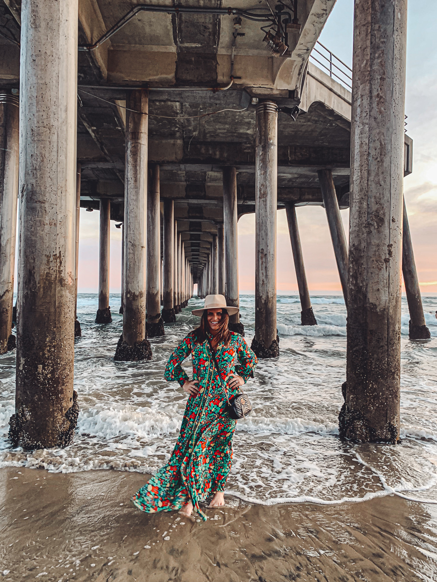 California Vacation Ideas for a Momcation in Orange County by popular Nashville travel blog, Modern Day Moguls: image of a woman standing in the ocean under a pier.