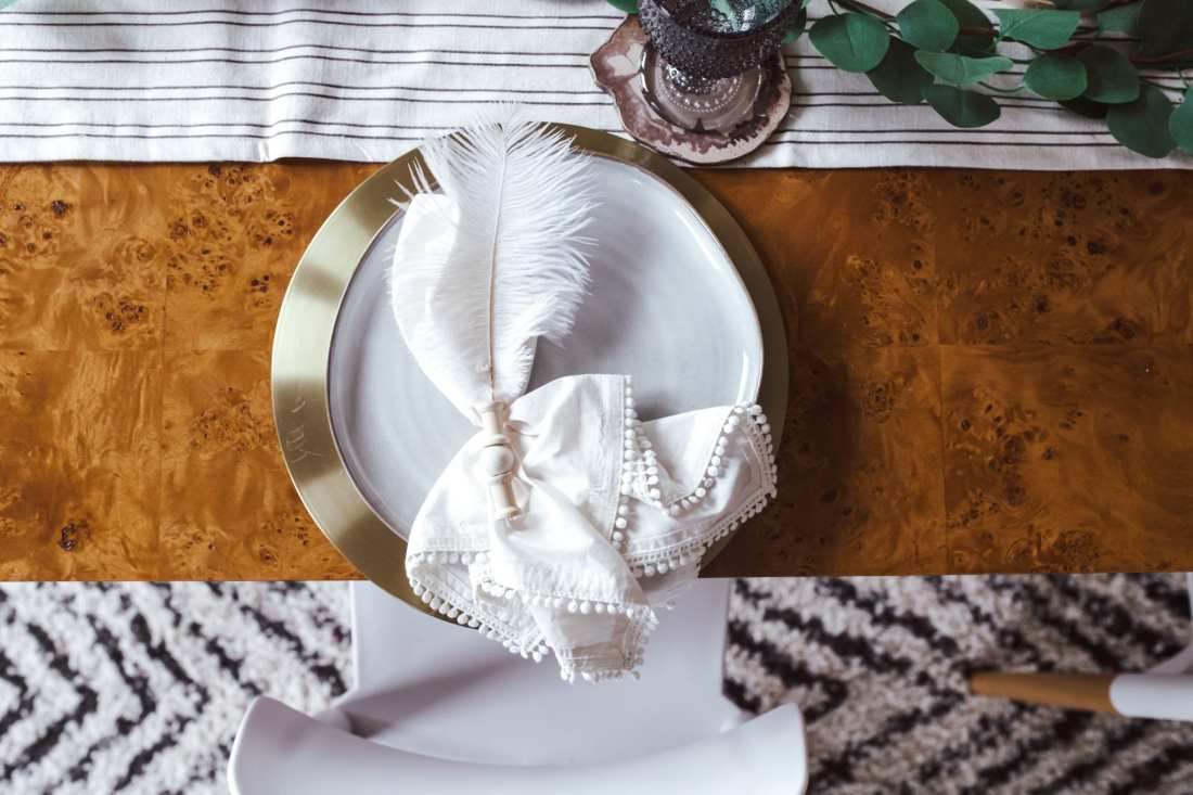 5 Ways to Decorate with Feathers for Boho Christmas Decor by popular Nashville lifestyle blog, Modern Day Moguls: image of a table decorated with Oriental Trading Eucalytpus Garland, Battery Operated Votive Candles, Feathers, Wooden Beads.