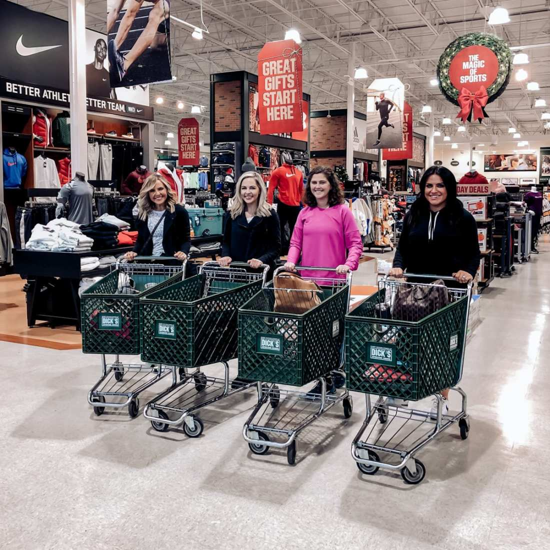 Unwrap the Magic of Sports with Dick's Gift Ideas by popular Nashville life and style blog, Modern Day Moguls: image of four Nashville bloggers with shopping carts at Dick's Sporting Goods.