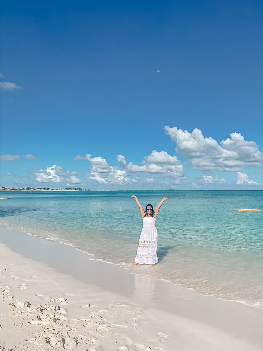 Visiting Turks and Caicos with Kids by popular Nashville travel blog, Modern Day Moguls: image of a woman standing in the ocean at Turks and Caicos.