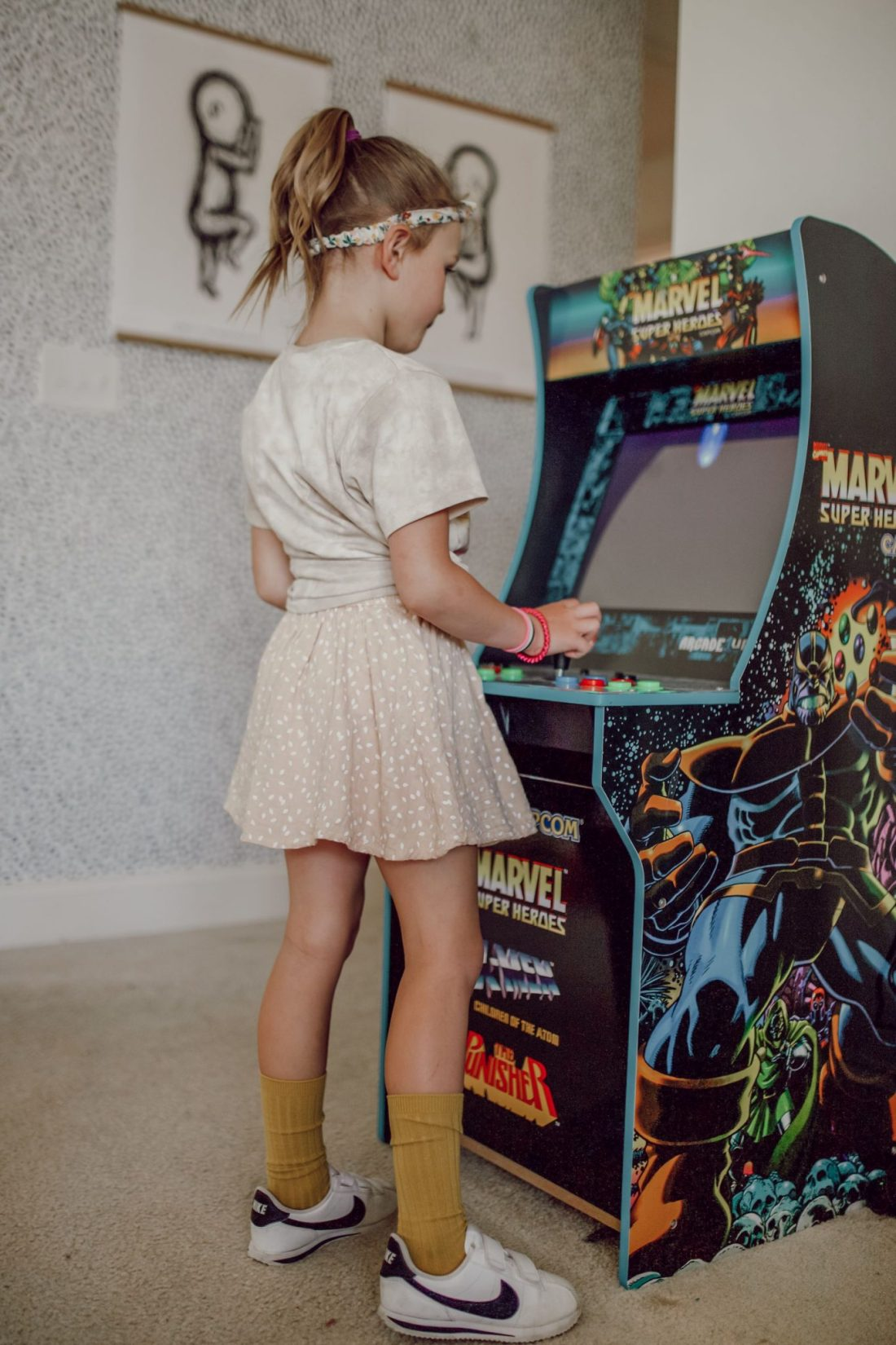 Homeschooling Journey by popular Nashville lifestyle blog, Modern Day Moguls: image of a little girl playing on a retro arcade game.