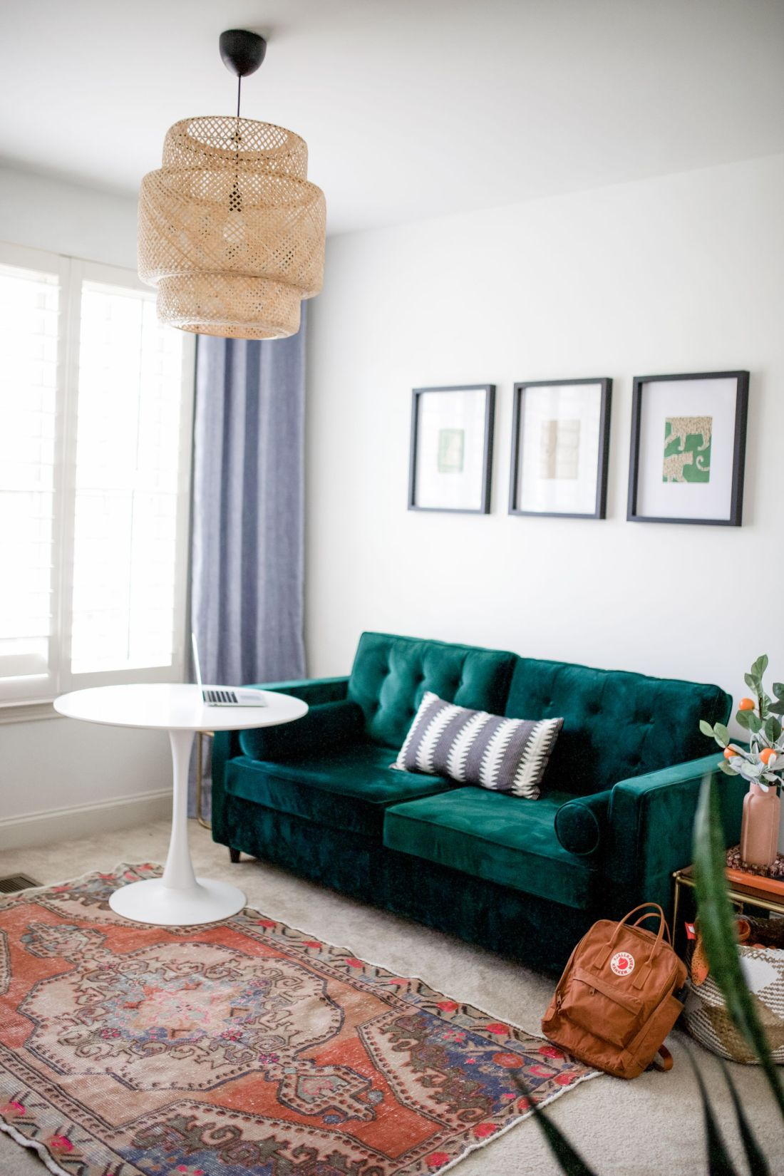 Homeshcool Room by popular Nashville life and style blog, Modern Day Moguls: image of a homeschool room with a tuft velvet couch, Persian rug, round white table, and wicker light pendant.