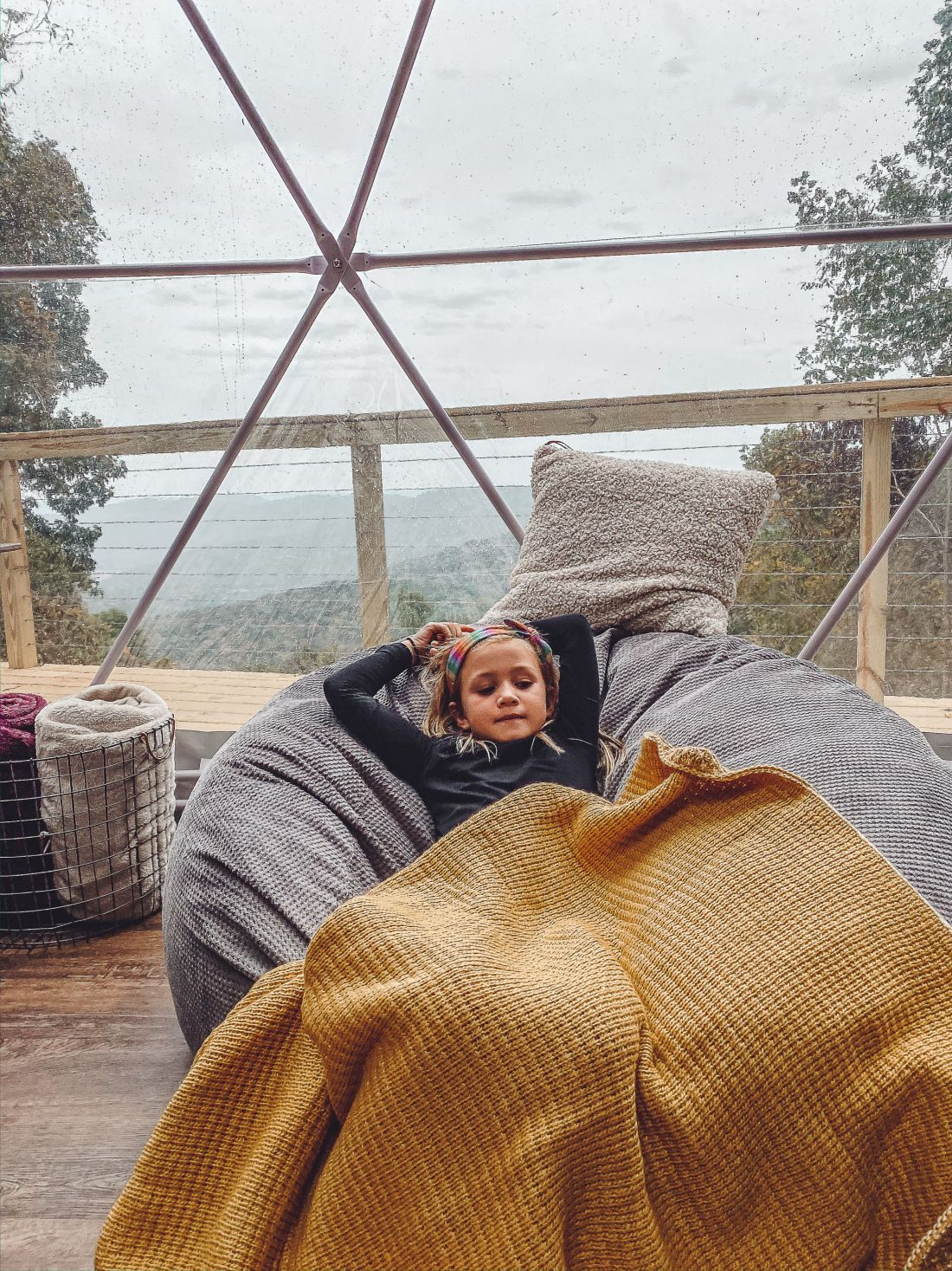 Glamping in Tennessee by popular Nashville lifestyle blog, Modern Day Moguls: image of a girl laying in a bean bag chair inside a geodesic dome.