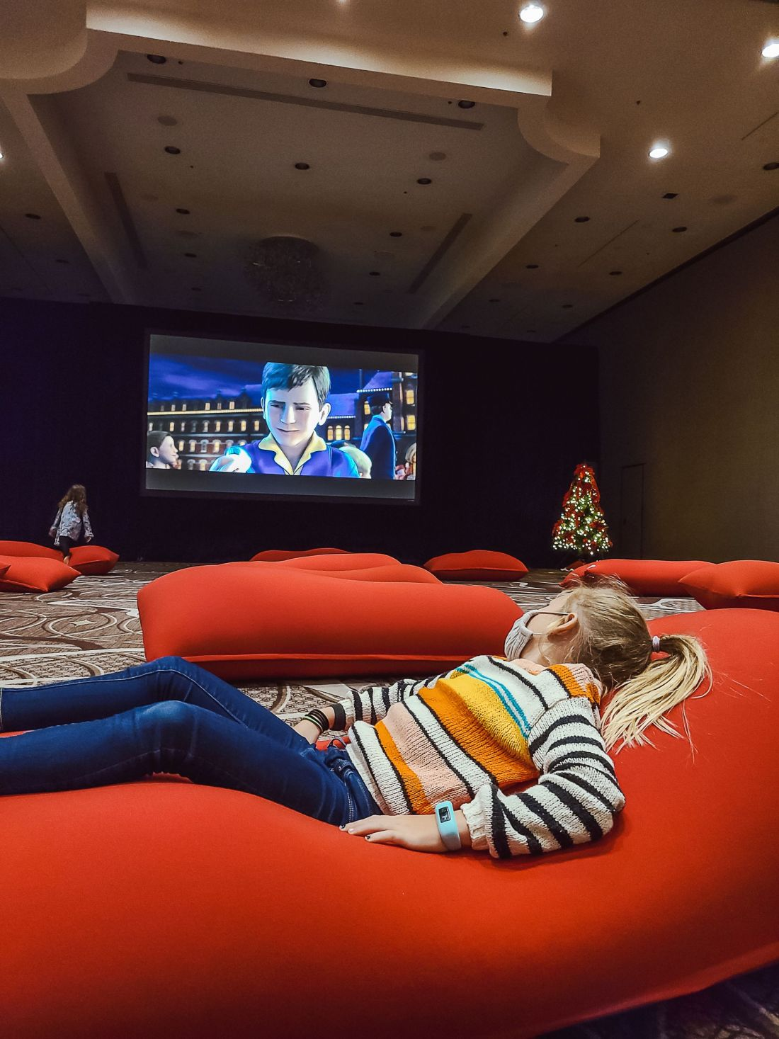 Gaylord Opryland Christmas by popular Nashville blog, Modern Day Moguls: image of a young girl laying on a red bean bag and watching the Polar Express on big screen.