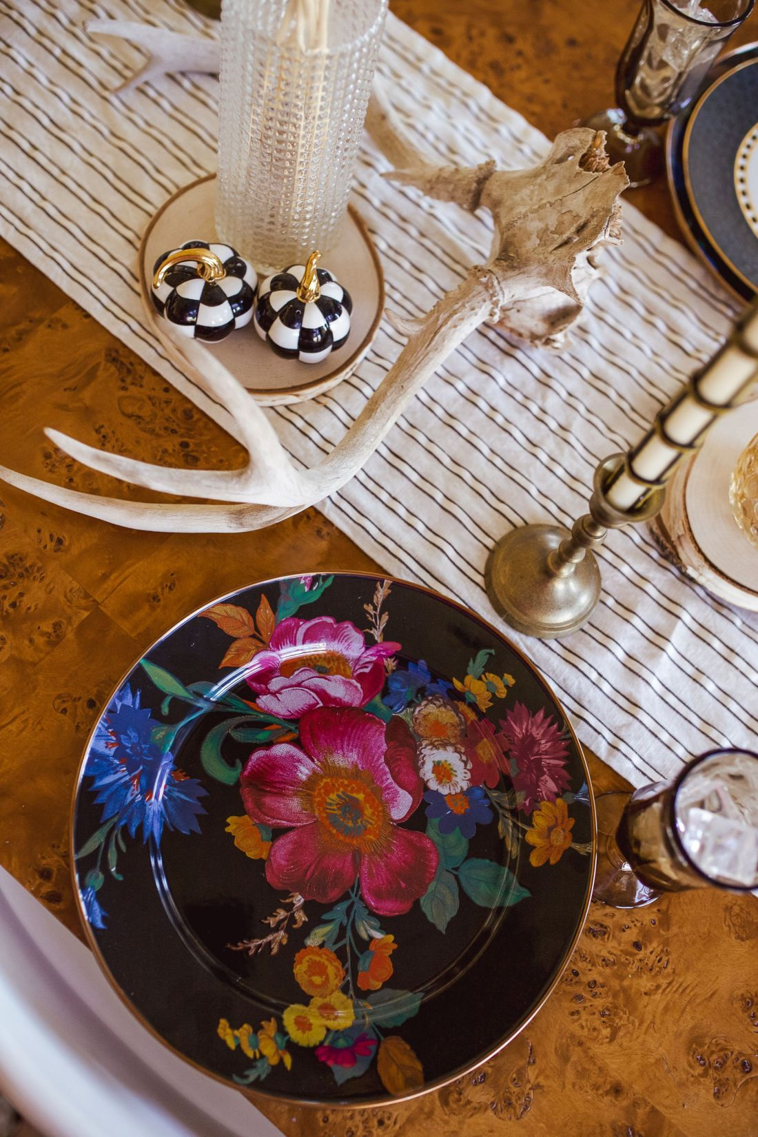 Christmas Tablescape Ideas by popular Nashville life and style blog, Modern Day Moguls: image of a table set with deer antlers, Mackenzie-Childs ceramic pumpkin black and white check salt and pepper shakers, floral glass plate, gold candlestick, blue plates and stripe table runner.