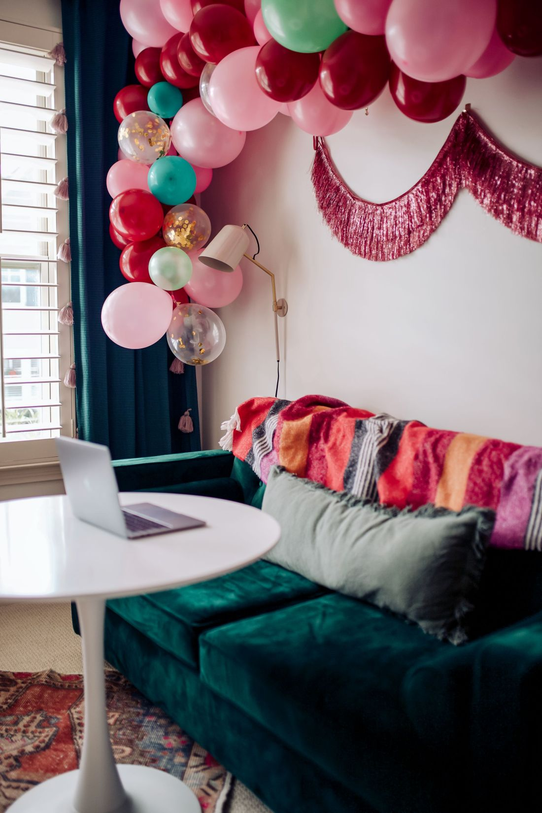 Carpet and Rug Institute by popular Nashville life and style blog, Modern Day Moguls: image of a home office decorated with a balloon garland, fringe tinsel garland, green velvet couch, white table and Carpet and Rug institute rug.