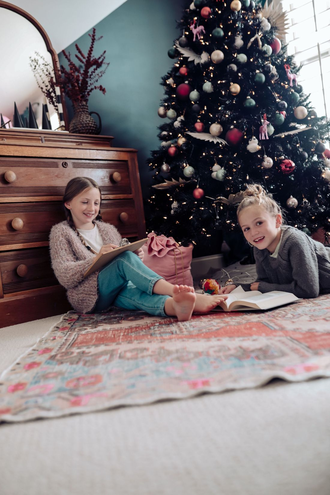 Carpet and Rug Institute by popular Nashville life and style blog, Modern Day Moguls: image of two girls in on a Carpet and Rug Institute rug in a home office decorated with a black Christmas tree and wooden dresser with a mirror.