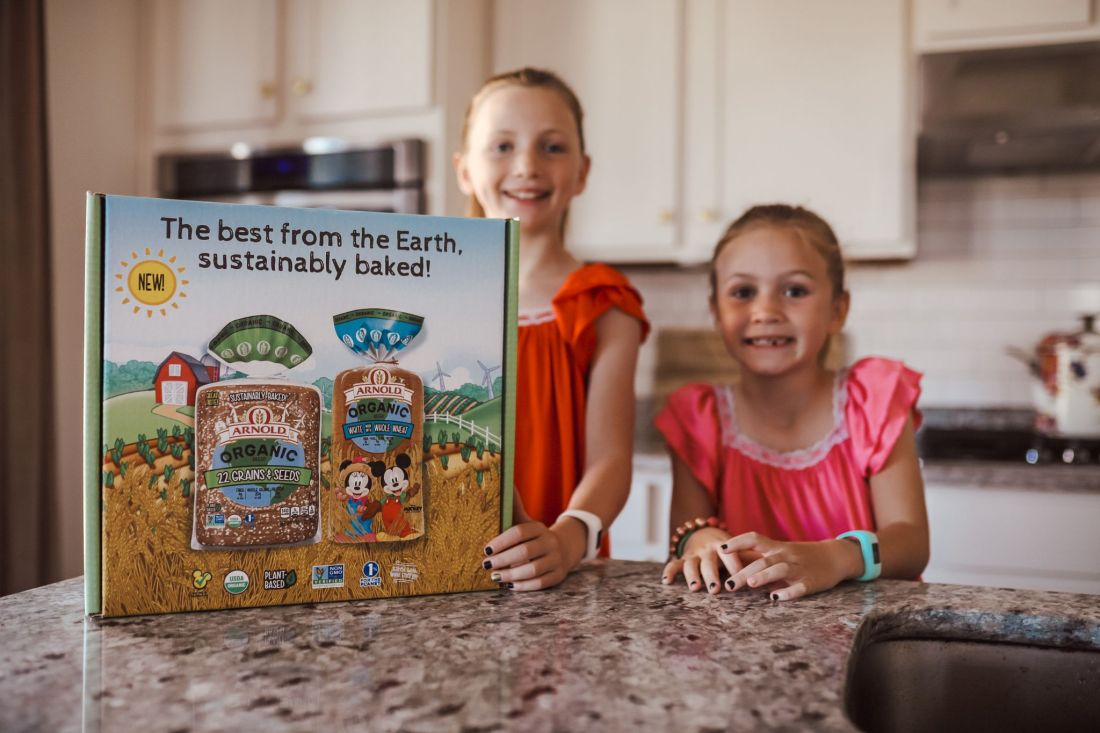 Kid Friendly Meal Ideas by popular Nashville lifestyle blog, Modern Day Moguls: image of two young girls standing in a kitchen next to a box of Arnold Organic Bread.