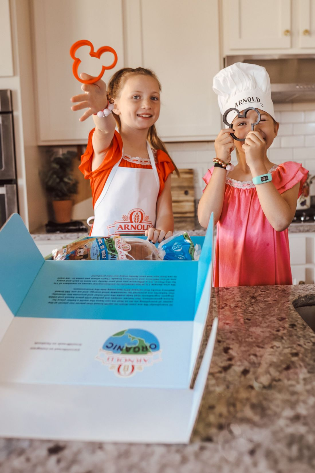 Kid Friendly Meal Ideas by popular Nashville lifestyle blog, Modern Day Moguls: image of two young girls wearing a chef hat and apron and holding Mickey Mouse shaped cutters in front of an open box of Arnold Organic Bread.