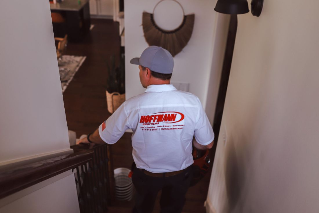 Purging Tips by popular Nashville lifestyle blog, Modern Day Moguls: image of a Hoffman Brothers employee walking down a flight of stairs inside a house.