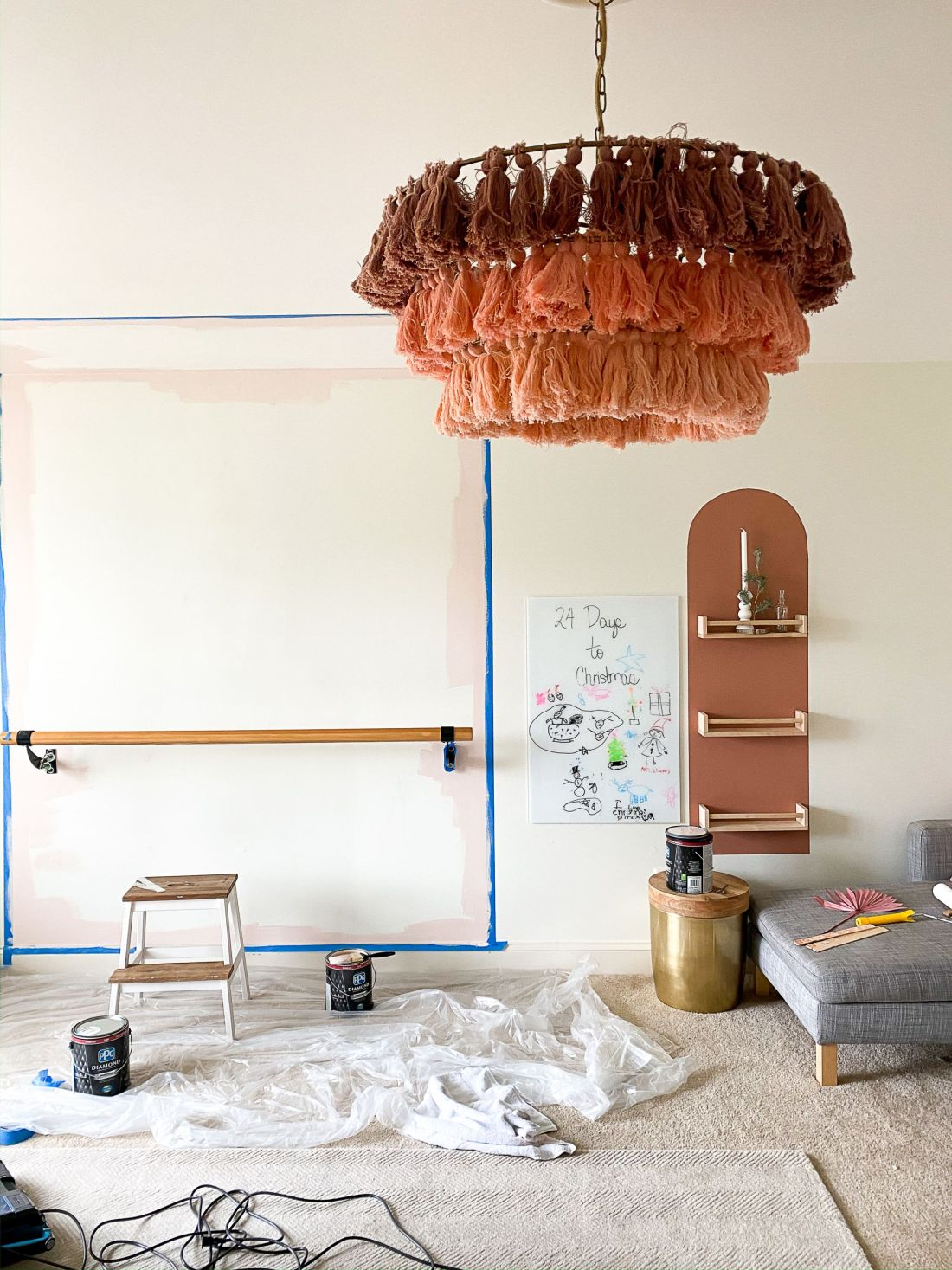 Geometric Shapes Design by popular Nashville life and style blog, Modern Day Moguls: image of a playroom with white walls, ballet bar, pink chairs, exercise trampoline, pink ombre tassel light fixture, and a grey sectional couch.