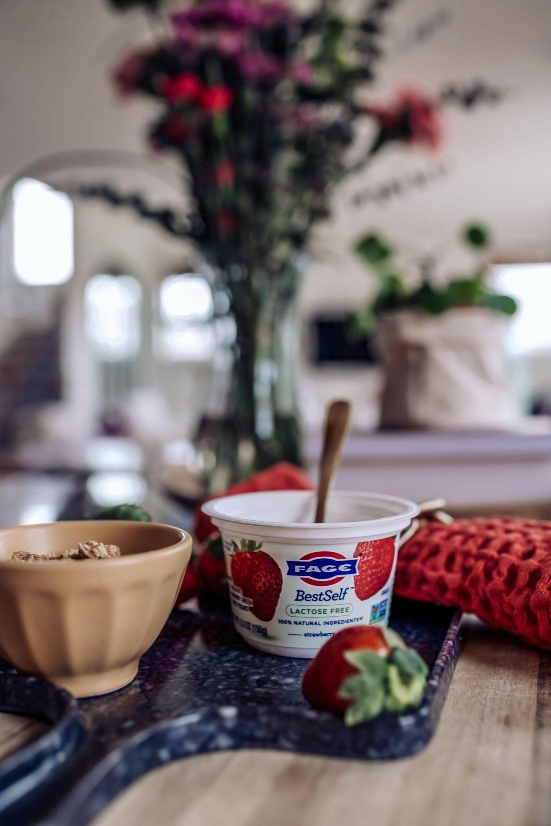 Keeping New Year's Resolutions by popular Nashville lifestyle blog, Modern Day Moguls: image of a Fage yogurt cup next to strawberries and a bowl of granola.