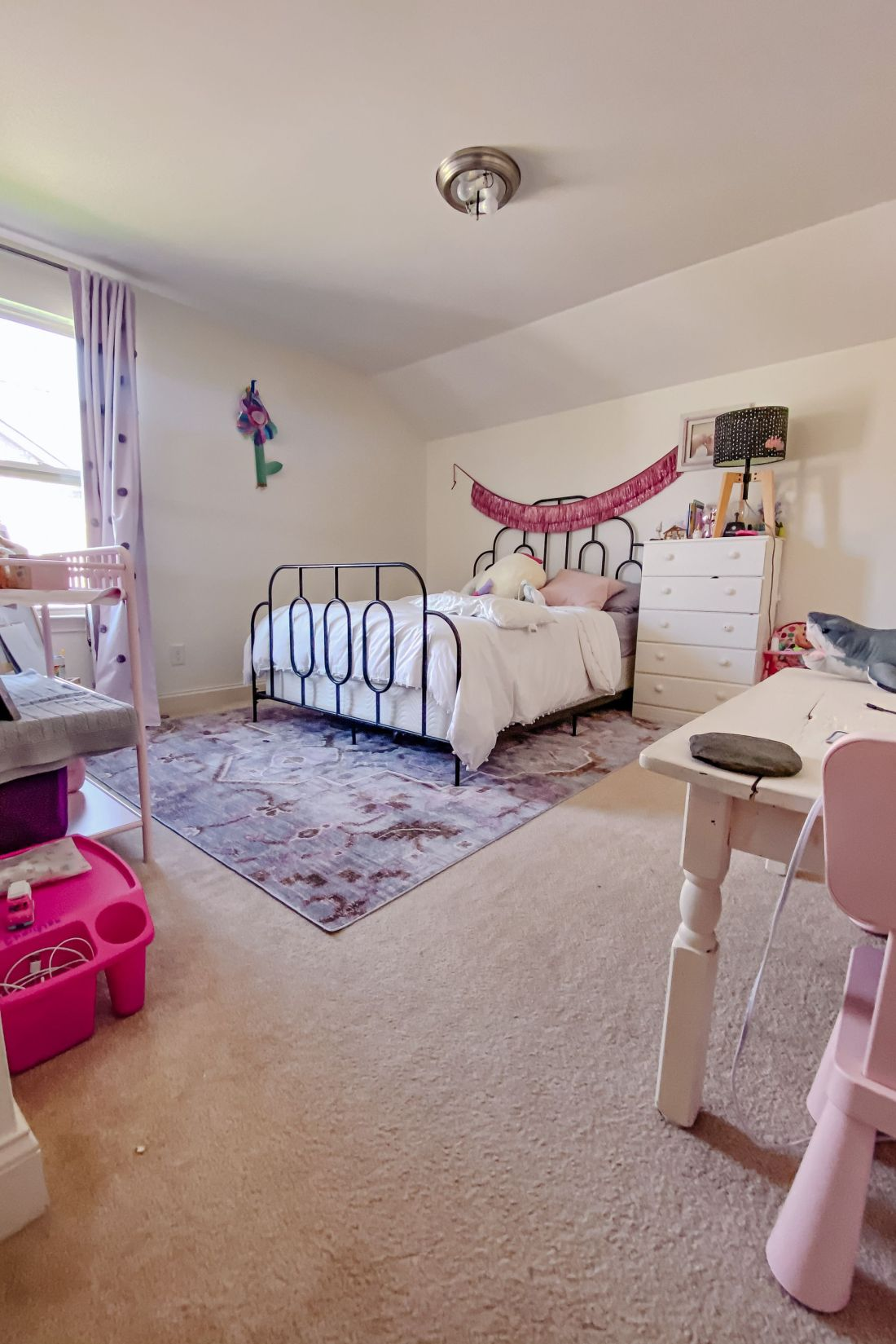 Kids Room by popular Nashville life and style blog, Modern Day Moguls: image of a girls room with a black iron bed frame, white dresser, pink desk with pink chair, black lamp with a black and white dot lamp shade, and purple area rug.