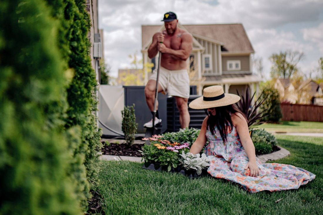 Spring Home Maintenance by popular Nashville lifestyle blog, Modern Day Moguls: image of a woman wearing a straw boater hat and floral dress while sitting outside next to a flower bed and some flowers while her husband is digging behind her with a shovel.