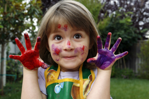 Close-up of a girl showing her hands painted with colors