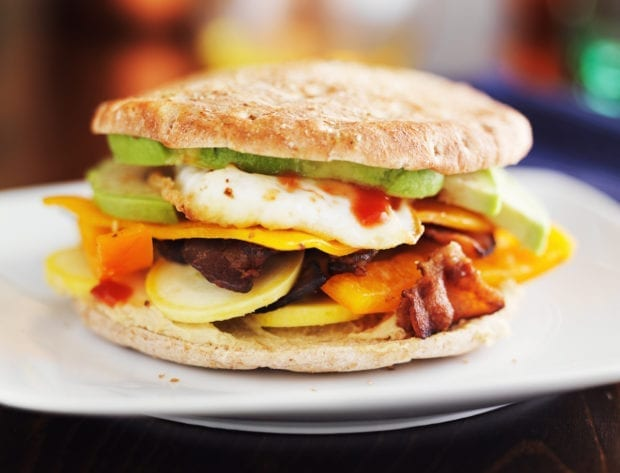 healthy breakfast sandwich with egg, bacon, avocado and vegetables