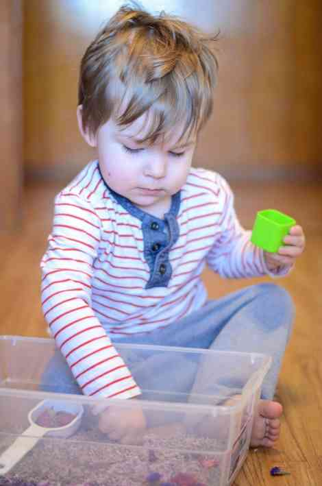 Toddler Playing With Sensory Bin